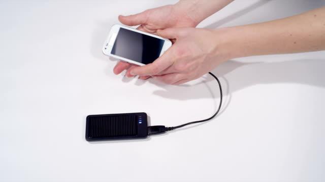unplugging smartphone off the solar charger - taşınabilirlik stok videoları ve detay görüntü çekimi