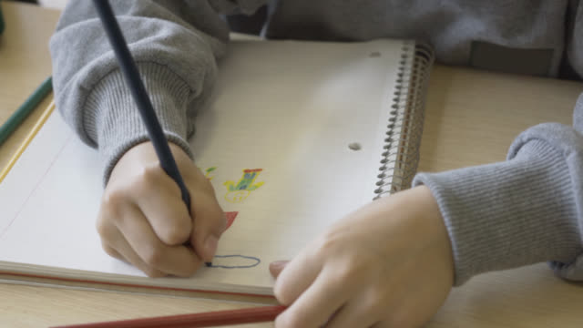 Unrecognisable child at school painting in his notebook video