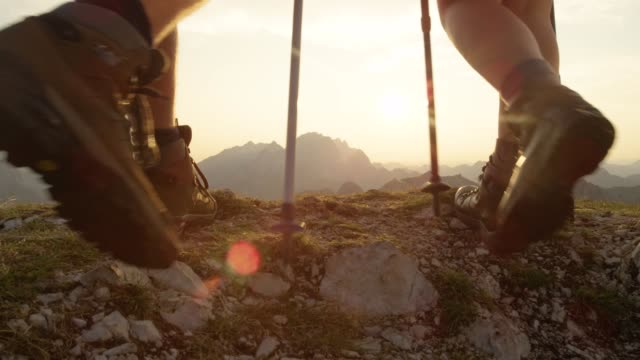 LENS FLARE: Unrecognizable active tourists walk up the mountain peak at sunrise. SLOW MOTION, LENS FLARE, CLOSE UP: Unrecognizable active tourists walk up the mountain peak at sunrise. Young couple wearing leather hiking boots reaches the stunning mountaintop at golden sunset. exploration stock videos & royalty-free footage