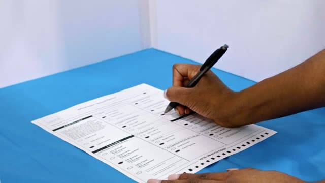 unrecognizable african american woman completes ballot on election day - vote filmów i materiałów b-roll