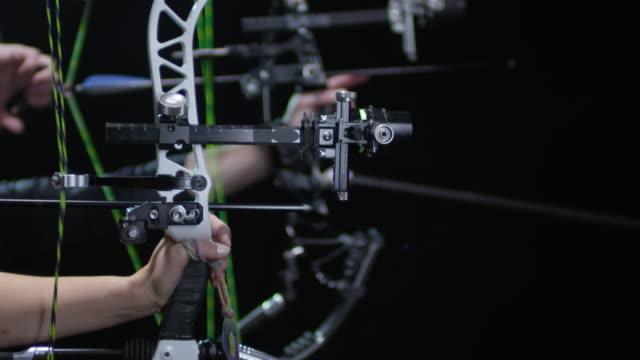 vidéos et rushes de méconnaissables archers tirant des arcs sur fond noir - tir à l'arc