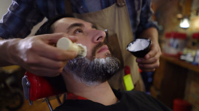 Unrecognizable barber putting shaving cream on the customers face video