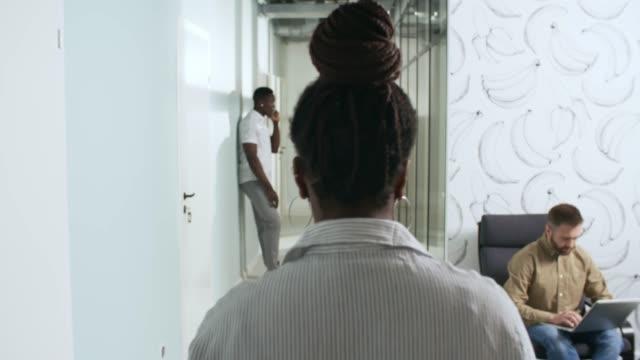 stockvideo's en b-roll-footage met onherkenbaar zwarte zakenvrouw wandelen langs office corridor - omgeving