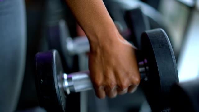 unkenntlich schwarze person, die die freie gewichte im fitnessstudio - gewichtstraining stock-videos und b-roll-filmmaterial