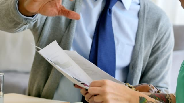 Unrecognizable business coworkers discuss financial documents