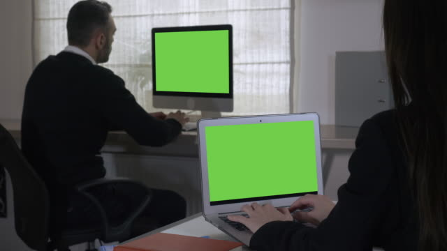 unrecognizable business team at work in room with two display screen video