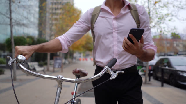Unrecognizable businessman commuting to work walking next to his bicycle while reading a text on smartphone