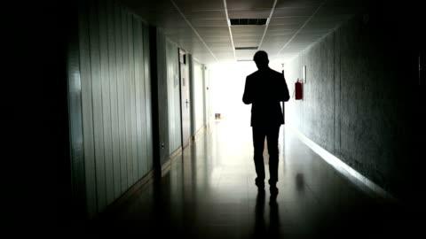 vídeos de stock e filmes b-roll de unrecognizable businessman working while walking in a dark hallway - fato