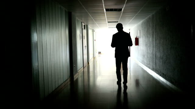 unrecognizable businessman working while walking in a dark hallway - completo video stock e b–roll