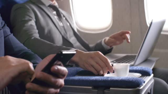 unrecognizable businesspeople on plane - kabina filmów i materiałów b-roll