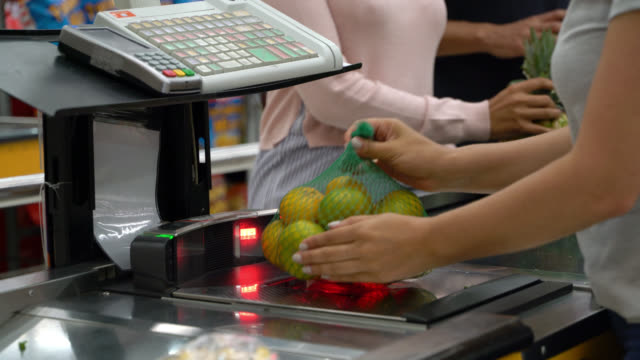 Unrecognizable cashier checking out customer couple passing products through the bar code reader Unrecognizable cashier checking out customer couple passing products through the bar code reader - close up register stock videos & royalty-free footage