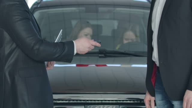 Unrecognizable Caucasian car dealer giving keys to successful client in front of vehicle with happy wife and daughter inside. Businessman buying family vehicle. Cinema 4k ProRes HQ.
