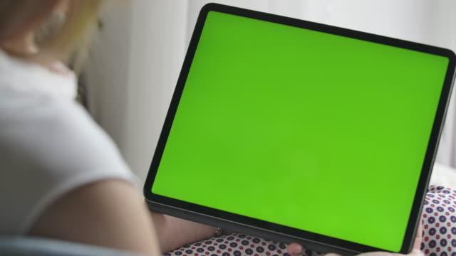 unkenntlich kaukasische frau hält tablet mit grünem bildschirm. nahaufnahme von chromakey auf dem gerät. moderne technologien, lebensstil. schießen über die schulter. kino 4k prores hq. - tablet mit displayinhalt stock-videos und b-roll-filmmaterial