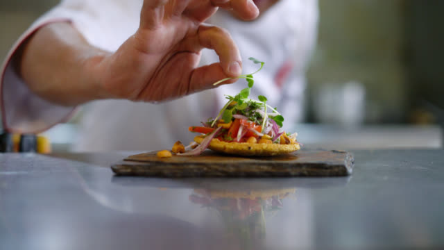unrecognizable chef decorating an appetizer on a stone plate - тарелки стоковые видео и кадры b-roll