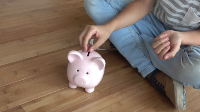 Unrecognizable child putting coins into a piggybank Unrecognizable child putting a lot of coins into a piggybank piggy bank stock videos & royalty-free footage