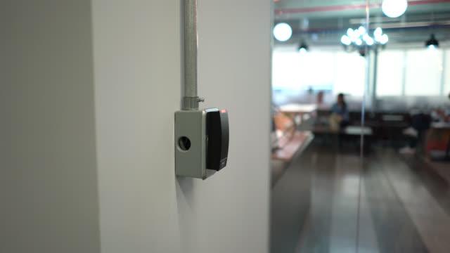 vidéos et rushes de des collègues méconnaissables entrent dans le bureau avec une clé de carte - porte entrée