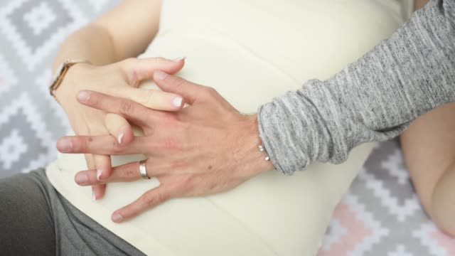 Unrecognizable couple holding hands on pregnant womans belly