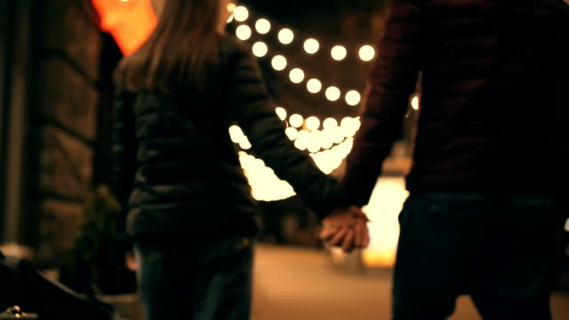 Unrecognizable couple holding hands walking along the night streets video