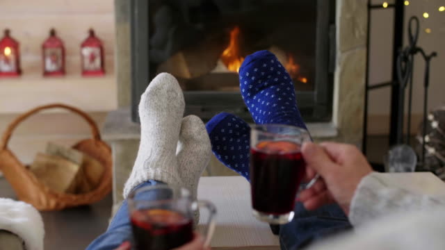 Unrecognizable couple relaxing by the fireplace Unrecognizable couple relaxing by the fireplace chalet stock videos & royalty-free footage