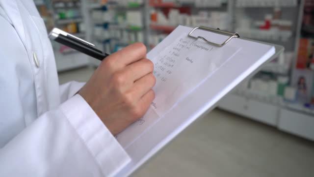 Unrecognizable doctor writing a medical prescription video