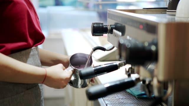 unerkennbare barkeeper mit moderner kaffeemaschine, um frisches getränk im café zu dampfen - milchkrug stock-videos und b-roll-filmmaterial