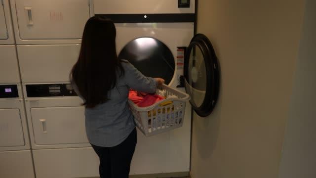 Clients femmes méconnaissable à une laverie automatique en tenant ses vêtements sur un panier à une machine de séchage - Vidéo