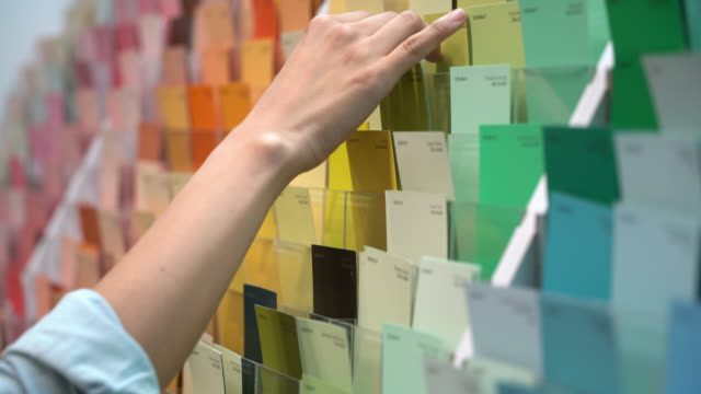 Unrecognizable female customer at a paint shop looking at color samples Unrecognizable female customer at a paint shop looking at color samples - Close up view renovation stock videos & royalty-free footage