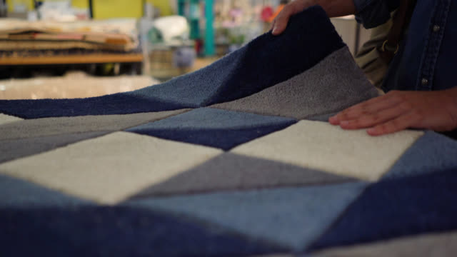 unrecognizable female customer feeling the texture of carpets at a furniture store - moquette video stock e b–roll
