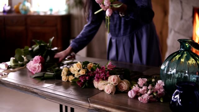 Unrecognizable female florist in blue dress is arranging flowers on the table, preparing for the future composition. Designing, floral workshop, leisure. Blurred picture of fireplace on the background