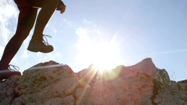 close up: unrecognizable female in leather walking boots climbing mountains - inerpicarsi video stock e b–roll