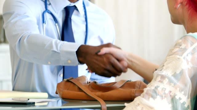 Paciente femenino de irreconocible estrecha la mano con doctor masculino - vídeo
