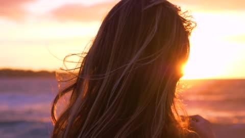 kadar yakın: tanınmayan kadın fotoğrafçı günbatımı okyanus üzerinde görünüyor. - rüzgar stok videoları ve detay görüntü çekimi