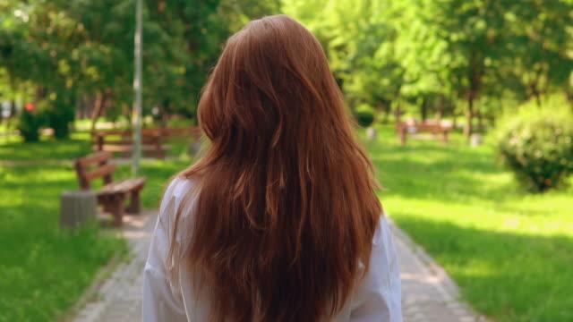 irriconoscibile passeggiata femminile nel parco - capelli rossi video stock e b–roll