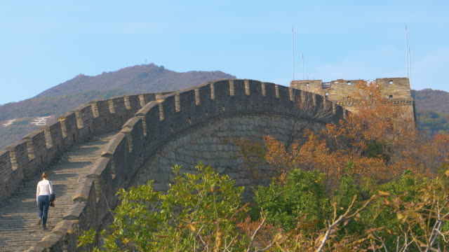 Unrecognizable female traveler walks up a flight of stairs atop the Great Wall.