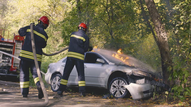 Unrecognizable firemen saving car from fire video