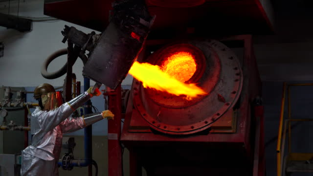 Unrecognizable Foundry Worker in protective clothing melts gold in the gold foundry video