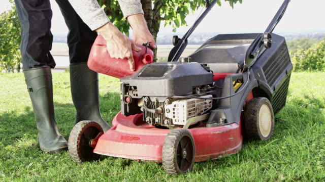 DS Unrecognizable gardener refueling a lawn mower Dolly shot of an unrecognizable gardener refueling a lawn mower parked in a garden. refueling stock videos & royalty-free footage