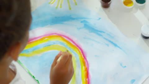 Unrecognizable Girl Drawing Rainbow at School High angle view of unrecognizable black girl using paint brush when drawing rainbow with watercolor during art lesson at school or in kindergarten art and craft stock videos & royalty-free footage