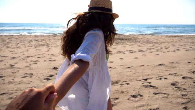 ragazza irriconoscibile che tiene la mano maschile e corre sulla spiaggia verso l'oceano. seguimi colpito da una giovane donna con il cappello che tira il suo ragazzo sulla riva del mare. concetto di vacanza estiva o vacanza. pov slow motion - braccio umano video stock e b–roll