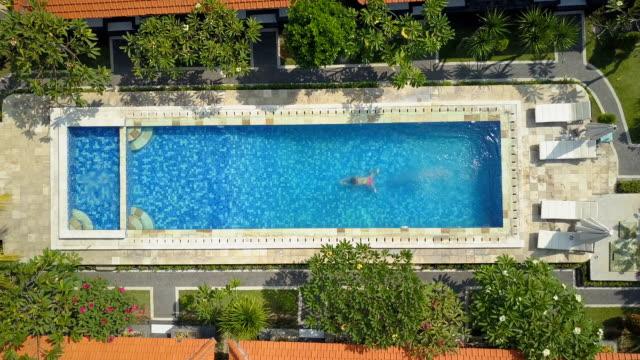 AÉREA de arriba abajo: irreconocible niña saltando nadando en la piscina en el resort de lujo - vídeo