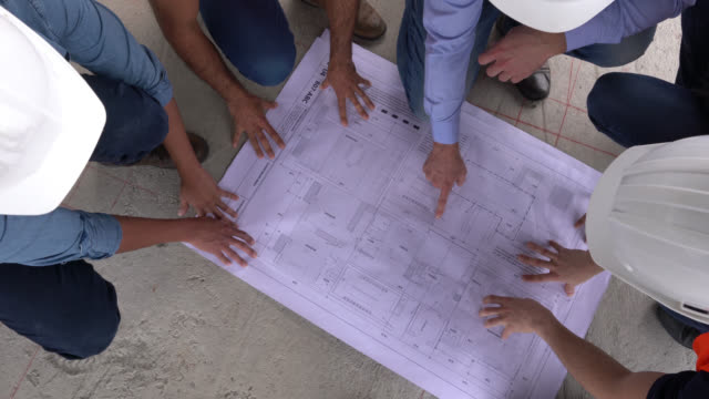 Unrecognizable group of architects, engineers and blue collar workers looking at a blueprint while man points at different things