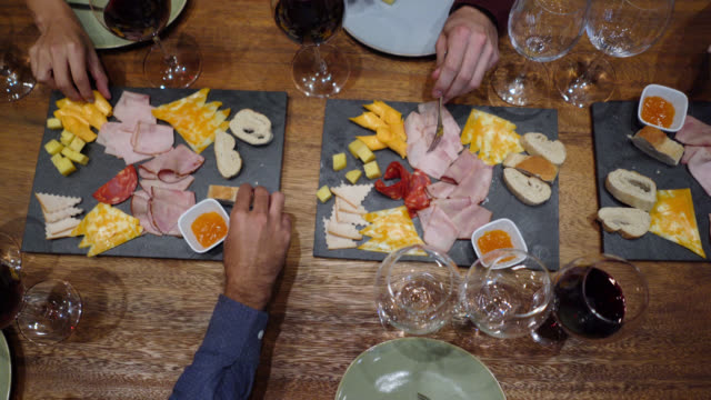 Unrecognizable group of friends enjoying cheese and ham during a wine tasting