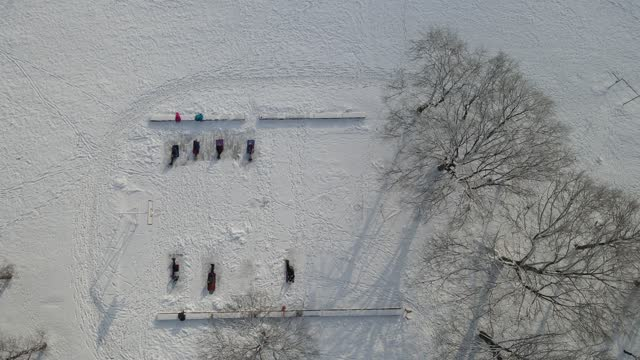 Unrecognizable group of people training on the basketball court covered by snow