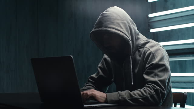Unrecognizable hacker man stretching hands and starting to typing on laptop and breaking password.