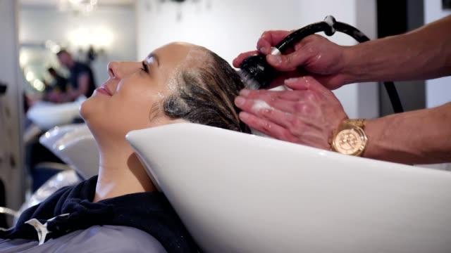 認識できないヘアー スタイリストがお客様の髪をリンスします。 - 美容室のビデオ点の映像素材/bロール