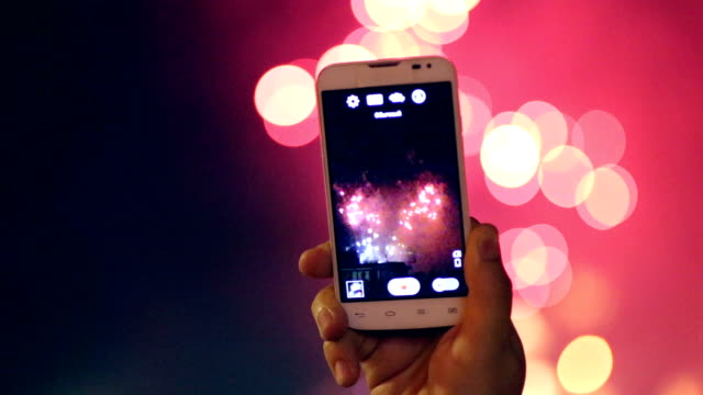 unrecognizable hand with smartphone filming and taking pictures of fireworks display. beautiful fireworks hd - chinese new year filmów i materiałów b-roll