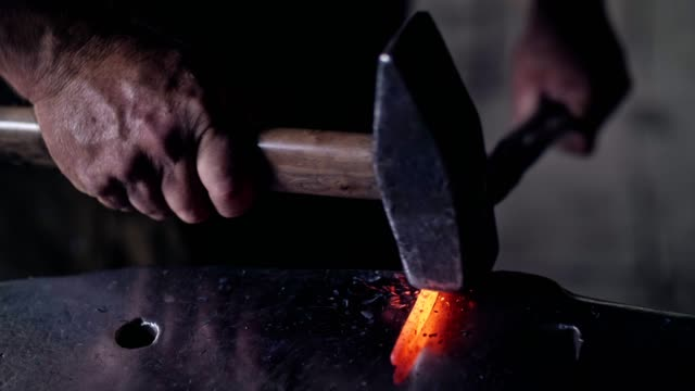 Unrecognizable hands of blacksmith. Unrecognizable hands of smith beat on glowing hot metal and sparks fly in all directions. 4k. slow motion. Blacksmith process. blacksmith stock videos & royalty-free footage