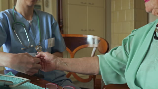 Unrecognizable healthcare worker measuring blood pressure of an old woman at home. video