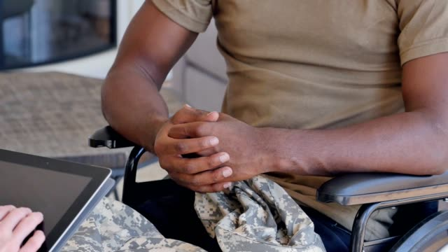 Unrecognizable injured military veteran discusses issues with female counselor Unrecognizable African American injured veteran talks with a female mental health professional about issues while serving overseas. The man is sitting in a wheelchair. He is gesturing while talking with the mental health professional. The counselor is using a digital tablet to take notes. veteran stock videos & royalty-free footage