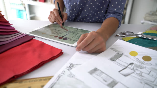 Unrecognizable interior designer working on tablet trying out colors on a design with fabric samples on table Unrecognizable interior designer working on tablet trying out colors on a design with fabric samples on table at a textile store interior designer stock videos & royalty-free footage